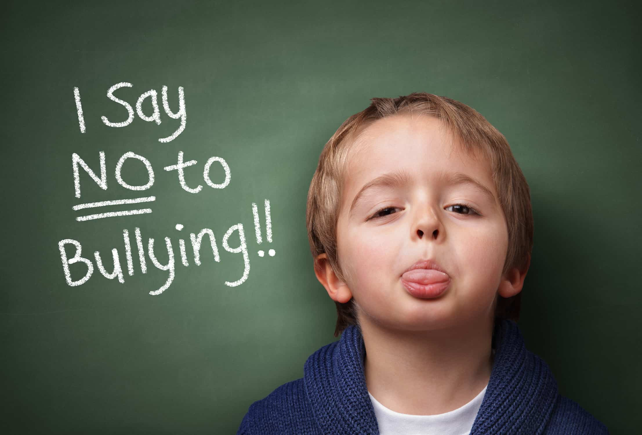 "Kid sicking his tongue out in front of a chalkboard that says ""I say No to Bullying!"""